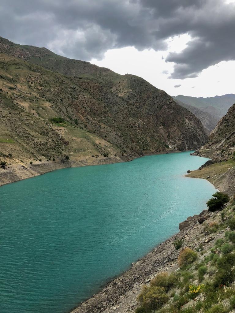 Beautiful emerald lake in Tajikistan with dramatic skies